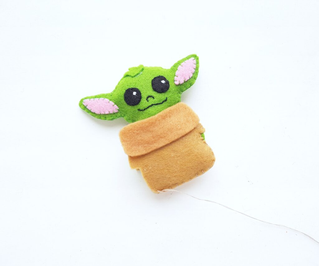 Baby Yoda being sewn shut completely.