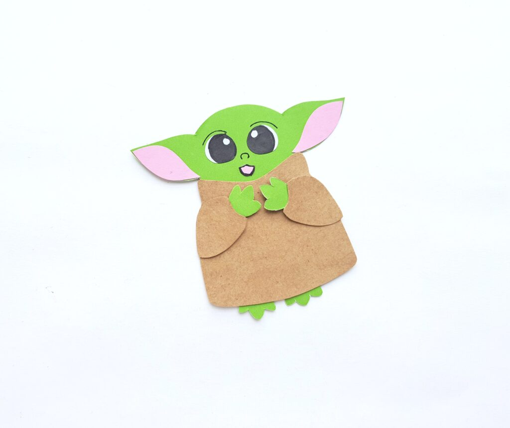 A mouth is glued on and a nose and eye lids drawn onto Baby Yoda's face.