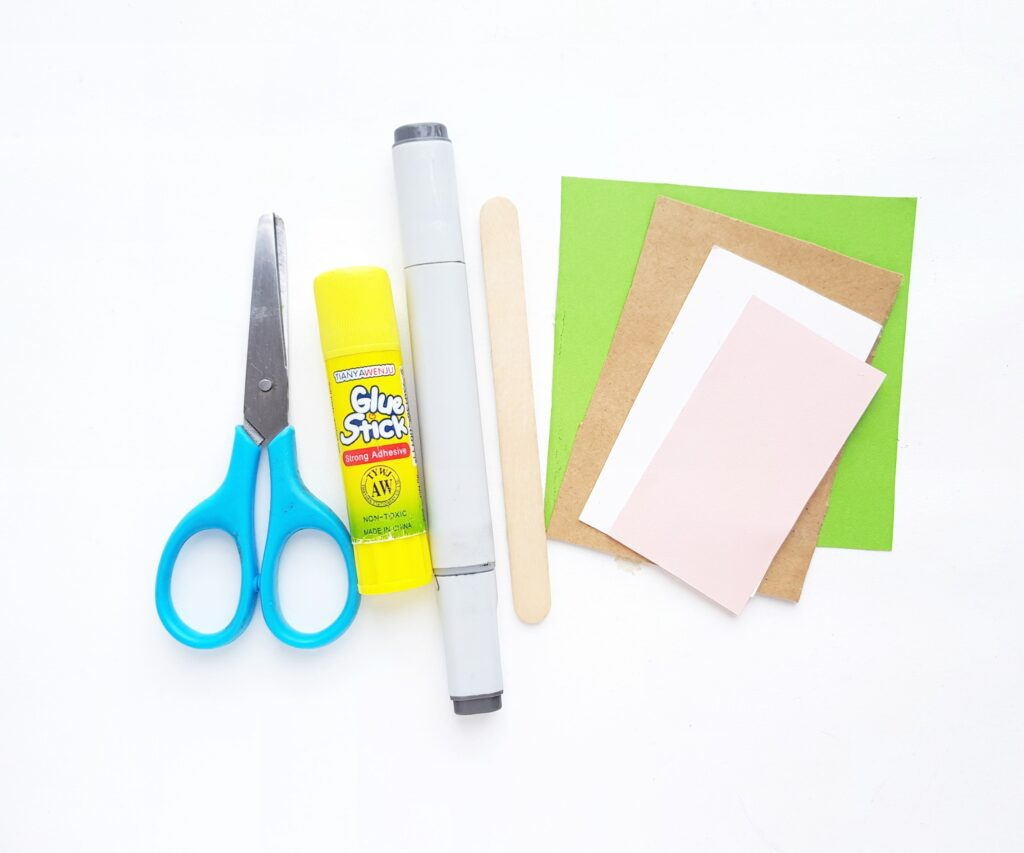 Supplies to make a Baby Yoda bookmark. Construction paper, glue, popsicle stick, scissors, and a marker.