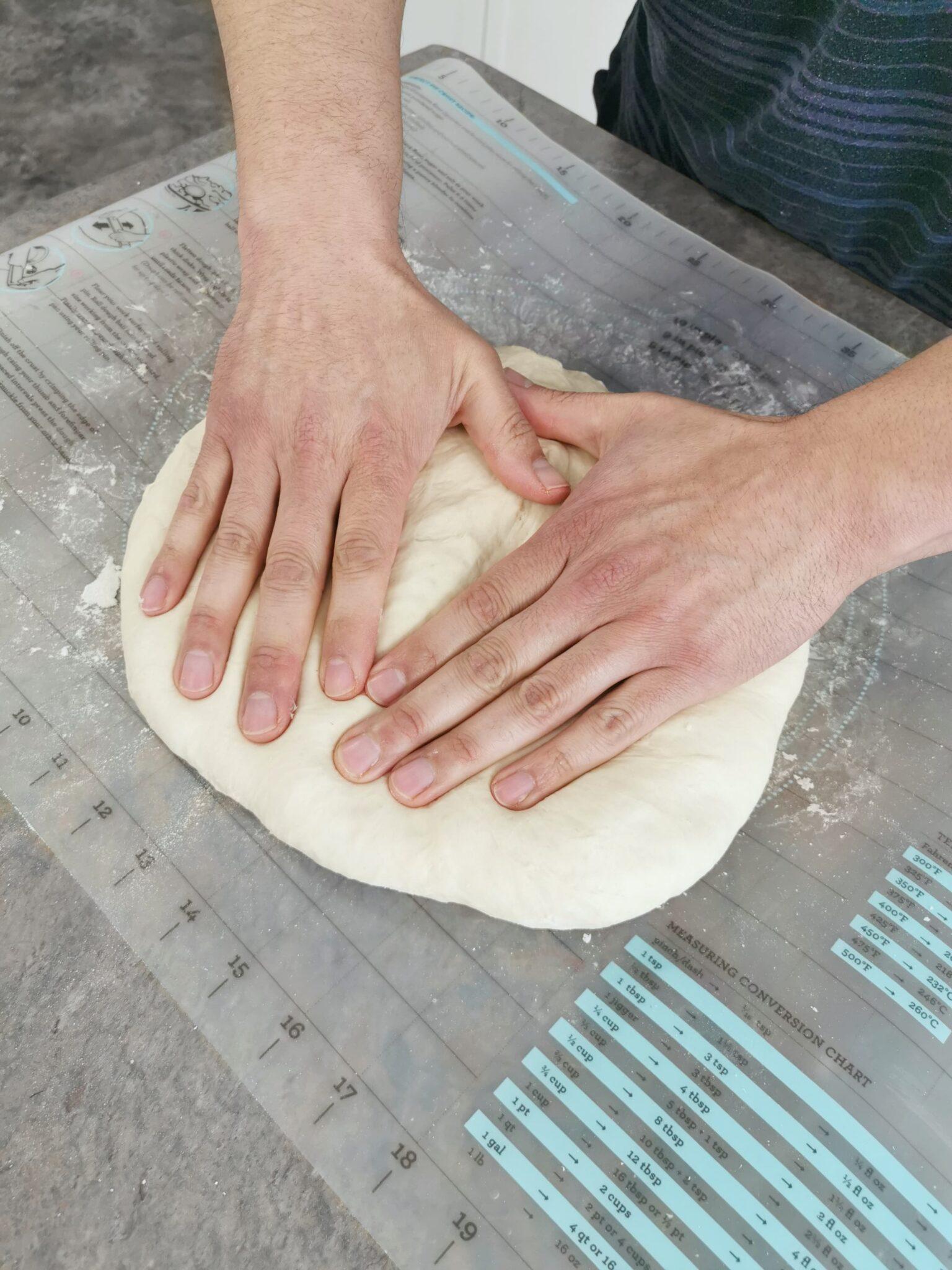 Flattening the dough.