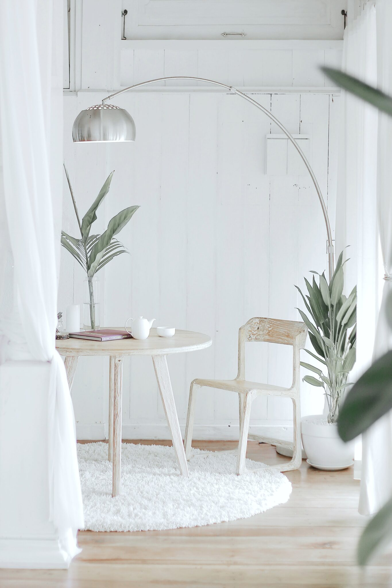 A white room with a table and chair, acting as a home office. There is a lamp that hangs over it.