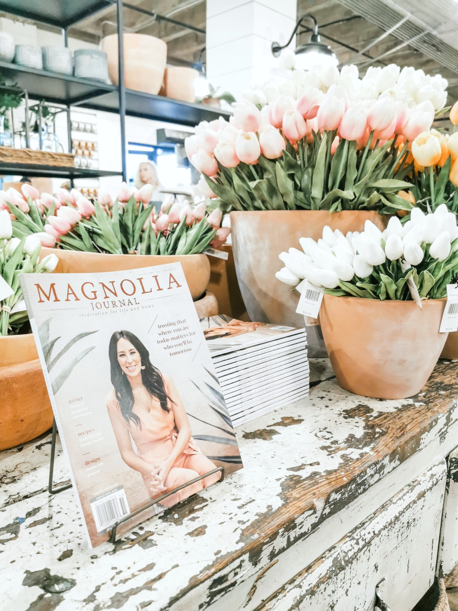 A Magnolia Market magazine on a rustic table with tulips.
