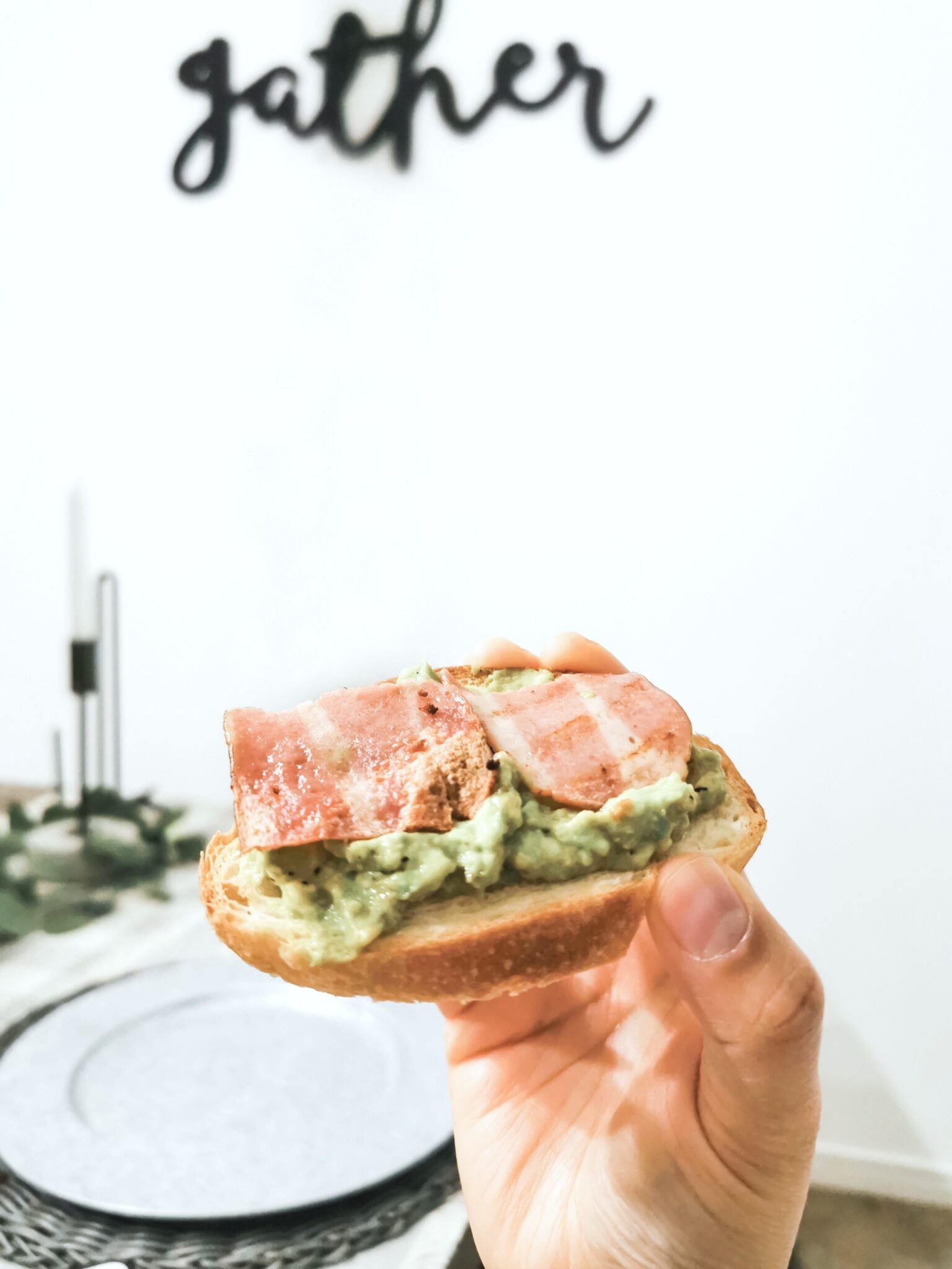 Nancy holds bacon avocado toast up to in her dining room.
