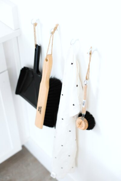 A white kitchen has hooks with cleaning supplies. This is how to prepare your home for summer.