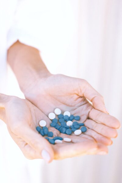 A woman's hand are shown holding handfuls of blue vitamins.