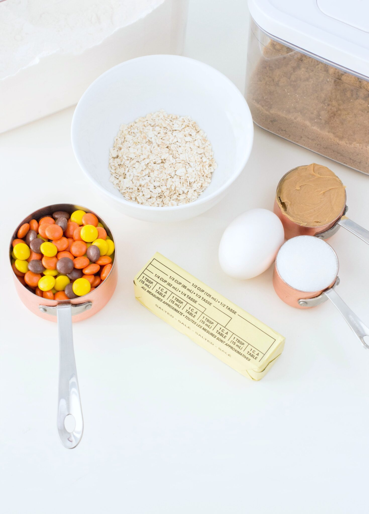 A cup full of Reese's Pieces, a bowl of brow sugar, oats, flour, eggs, peanut butter, and butter are shown as ingredients needed for Reese's Pieces Oatmeal Peanut Butter Cookies.