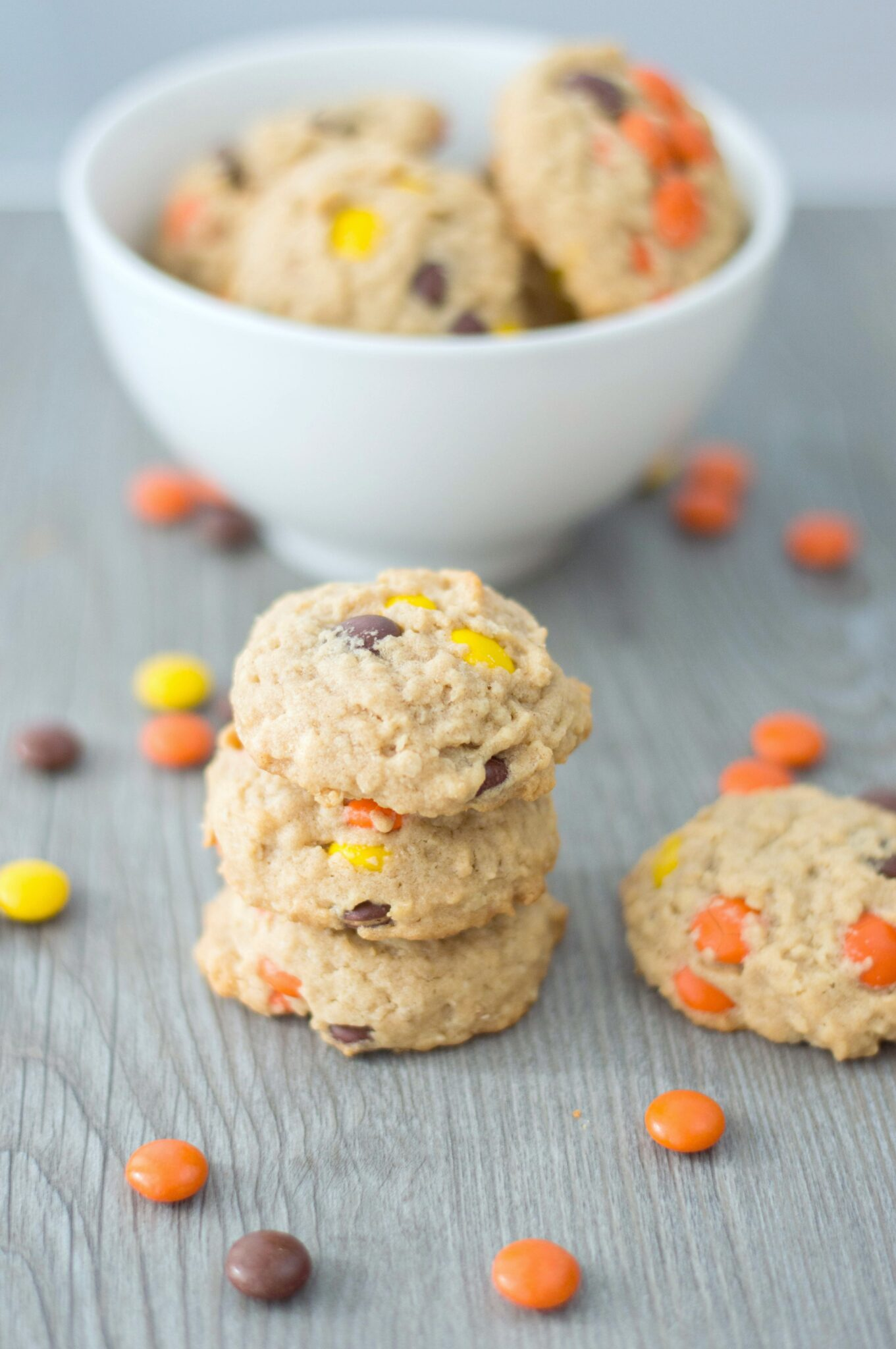 A bowl of Reese's Pieces Oatmeal Peanut Butter cookies with a stack of cookies on a grey tabletop.