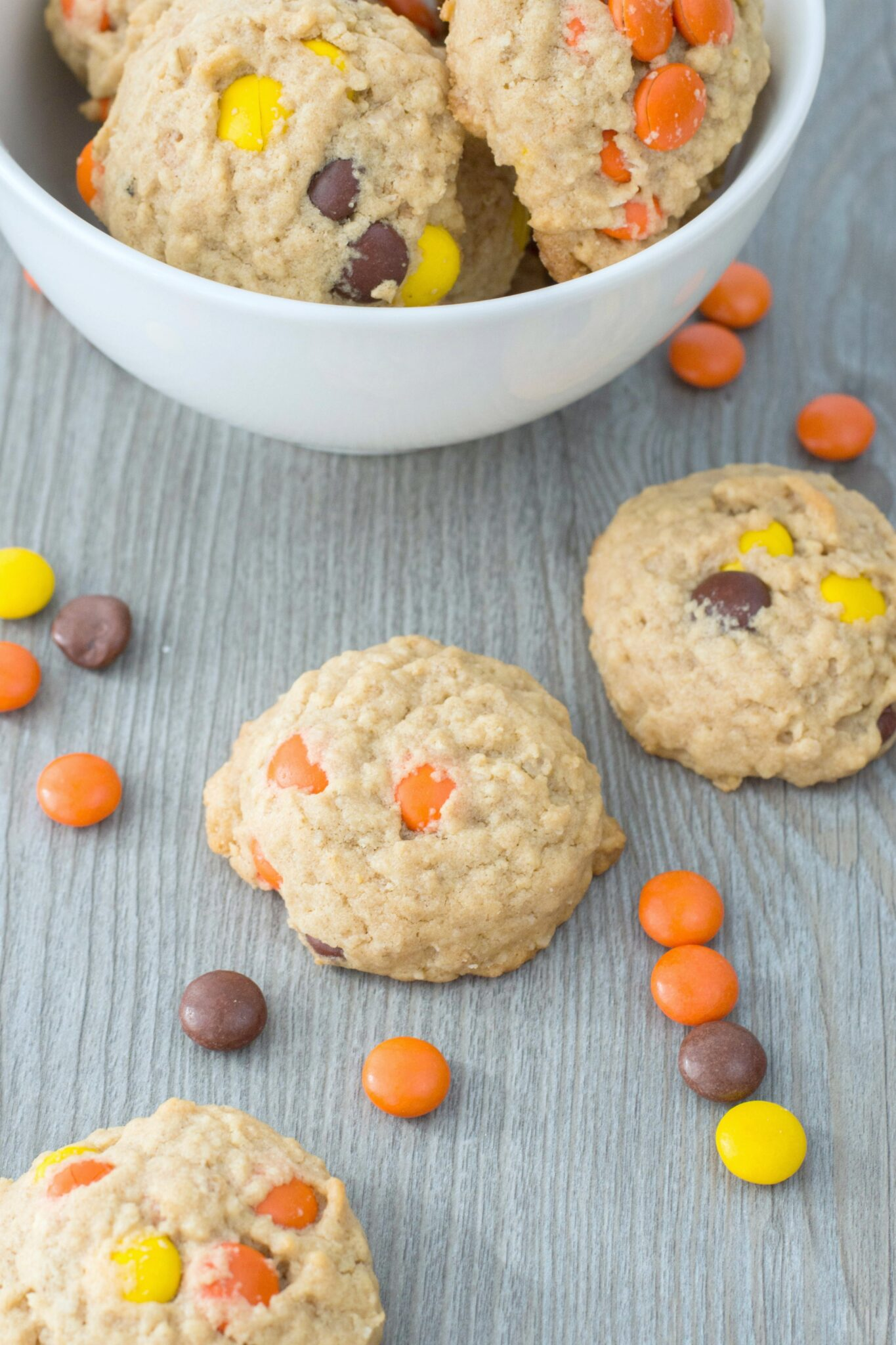 A bowl full of Reese's Pieces Oatmeal Peanut Butter cookies with 3 cookies on the table surrounded by Reese's Pieces. They sit on a grey table.