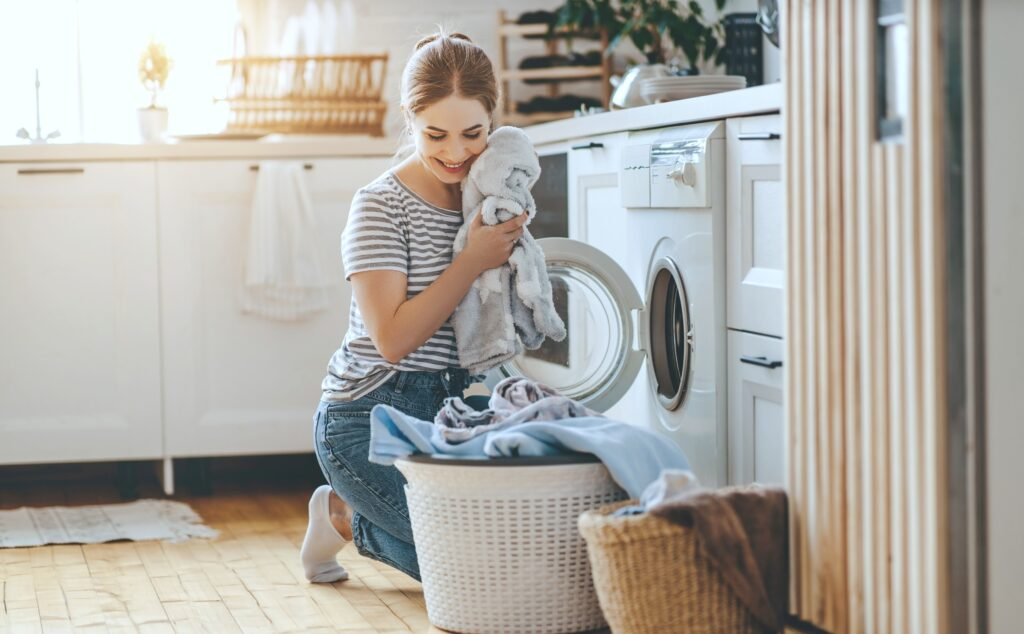Woman takes out laundry from front facing washing machine. She smiles and holds a clean towel to her face while she loads the basket.