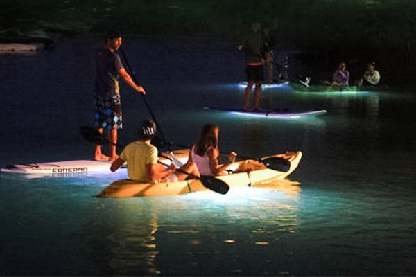 A couple kayak on a lake at night time.