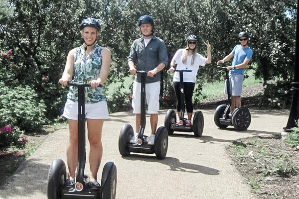 A family of 4 rides Segways on a tour.