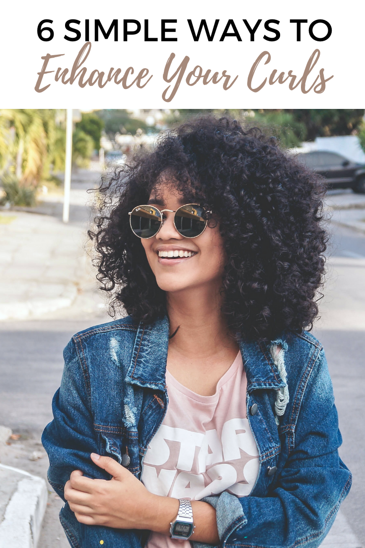 A beautiful black woman smiles and looks away from the camera. She is wearing glasses and has beautiful curls.