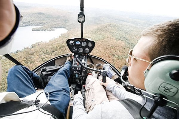 Two men fly a helicopter over wooded area.