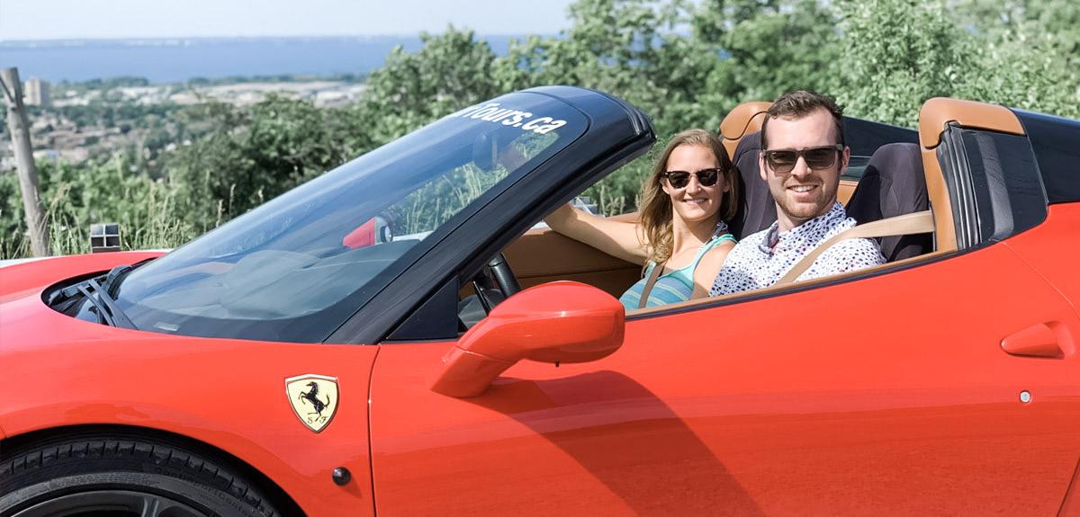 A man and a woman drive an exotic car, a red Ferrari.