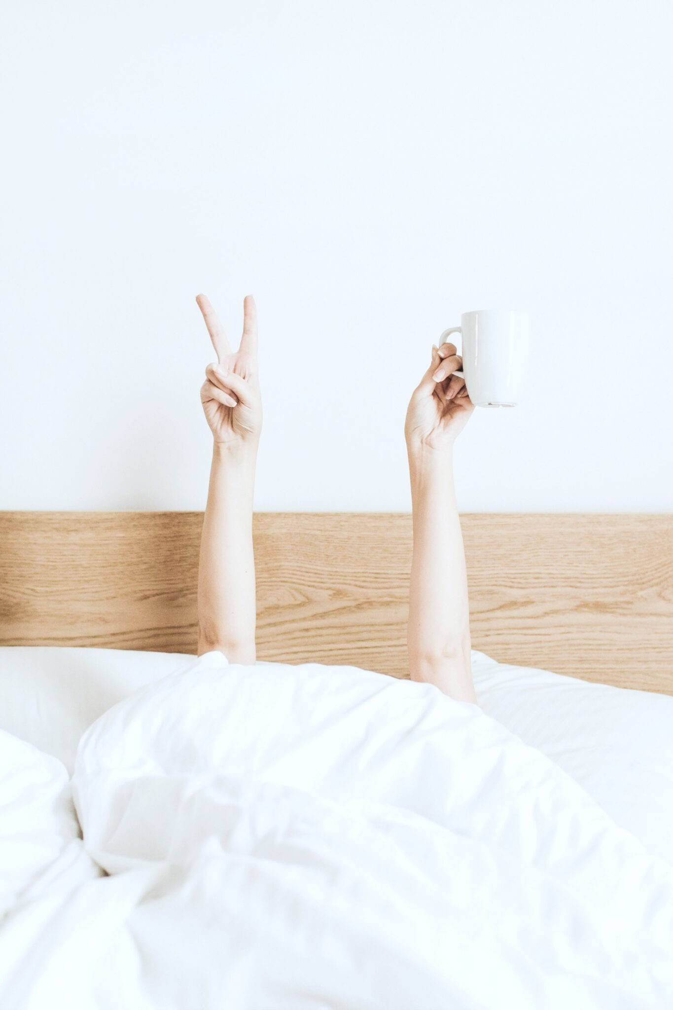 A woman hides under her sheets in bed and raises a peace sign and a coffee mug.