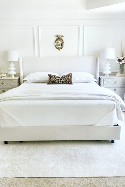 A beautiful, clean, white bedroom, that is tidy. It has a small mirror above the bed. The bedroom is to signify and share the 5 things you should have in your room to keep it tidy.