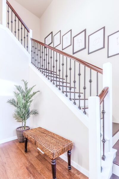 A beautiful staircase with a bench and houseplant. This article is about the best upgrades for first time homeowners.