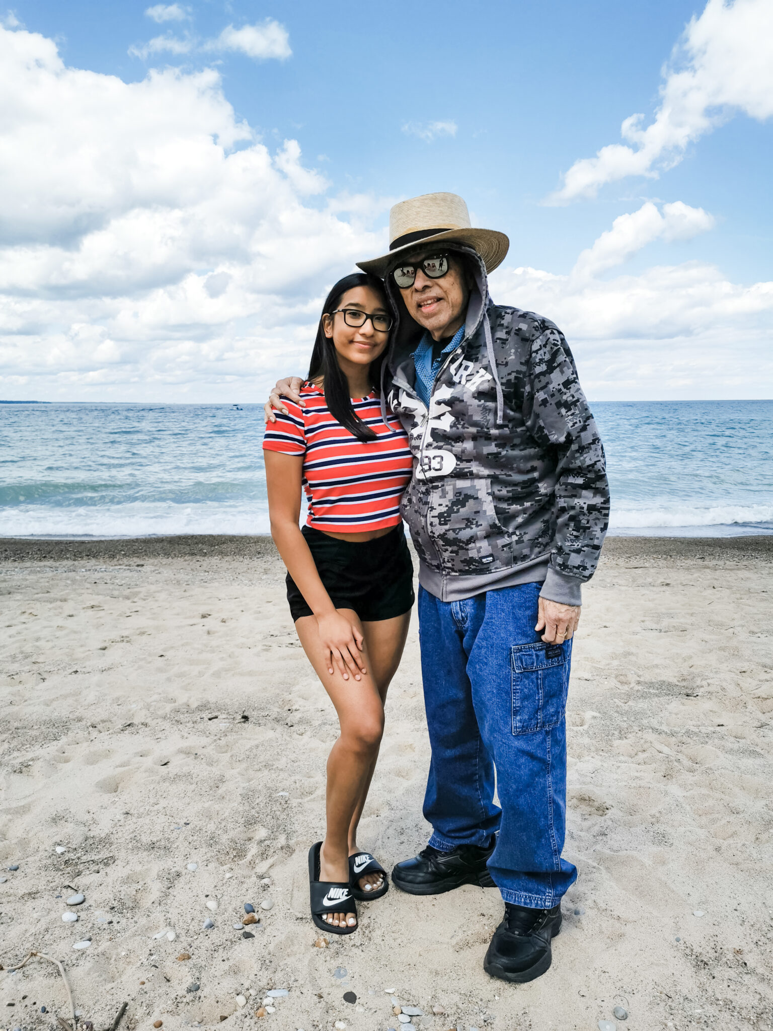 Gabby and her Abuelito posing ont he beach, they are both smiling.