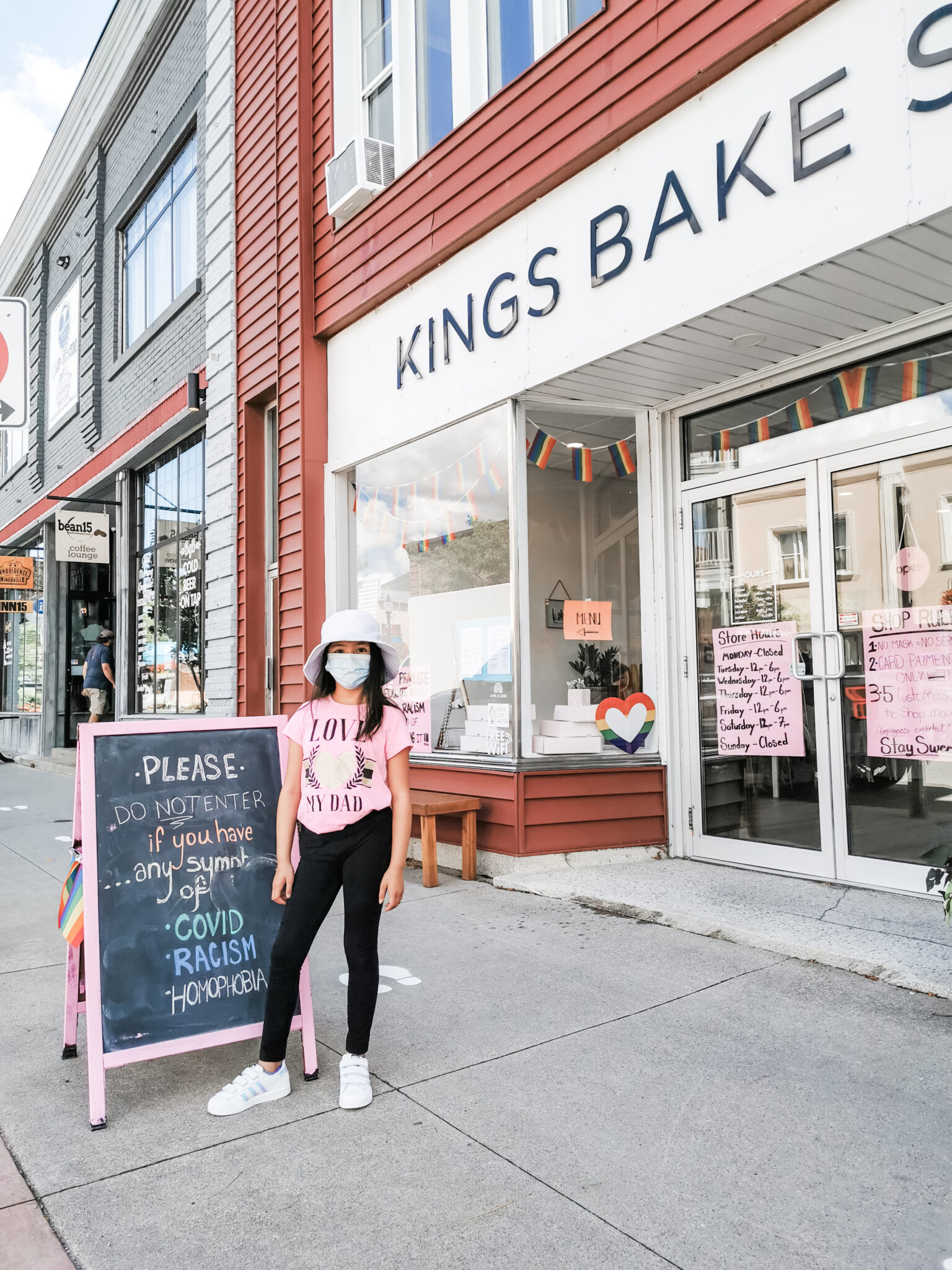 Mimi wearing a mask in front of King's Bakery.