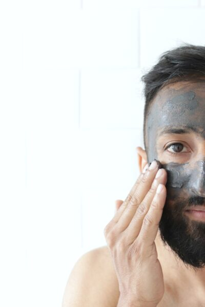 Man puts clay mask on his face and looks straight ahead.