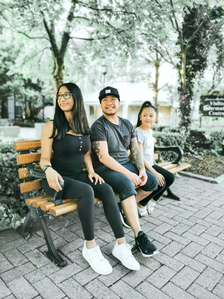 Gabby, Darasak, and Mimi sit on a bench in Amherstburg.