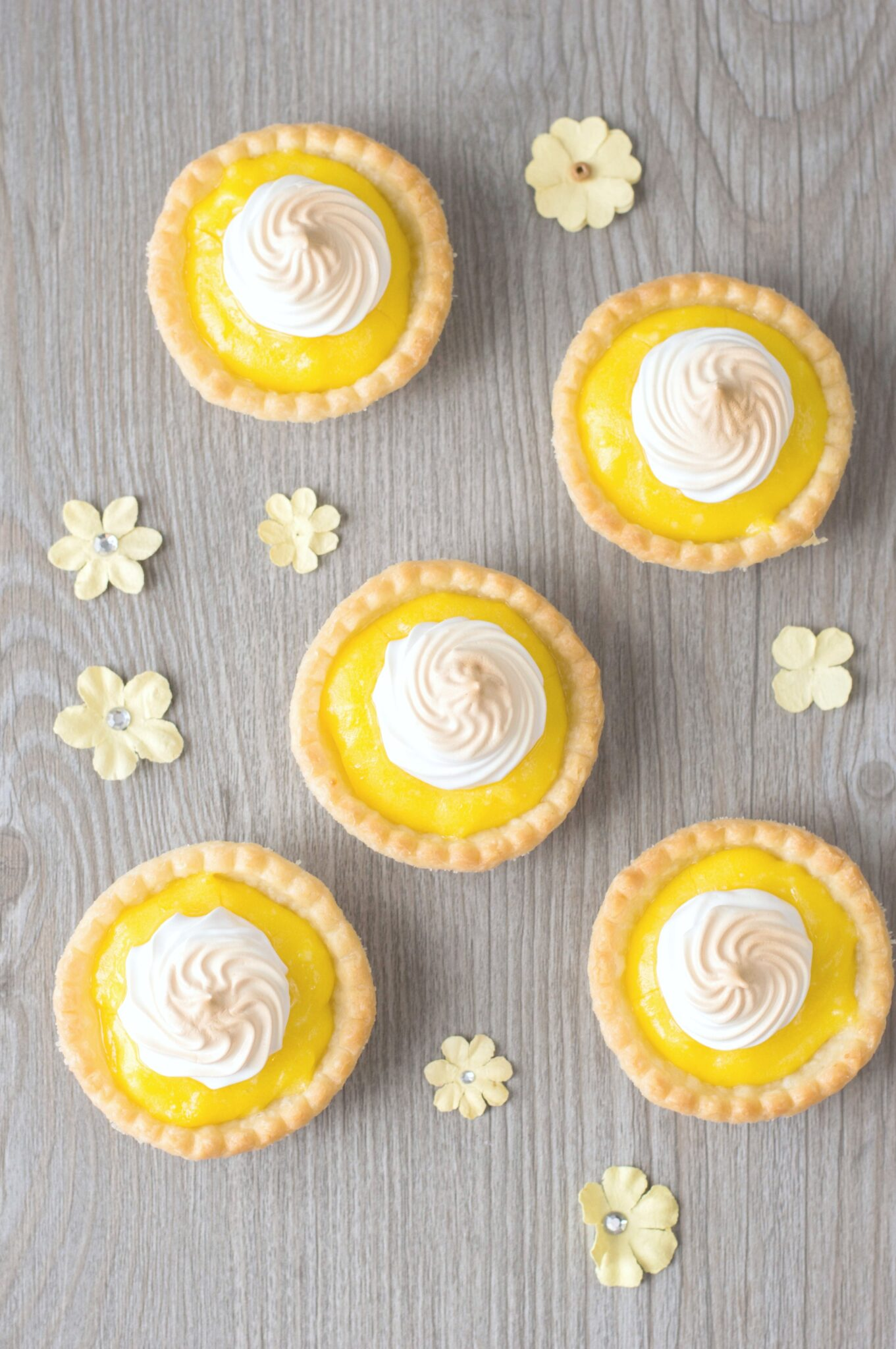A flat lay view of Mini Lemon Meringue Tarts on a wooden board. Yellow flowers decorate the board.