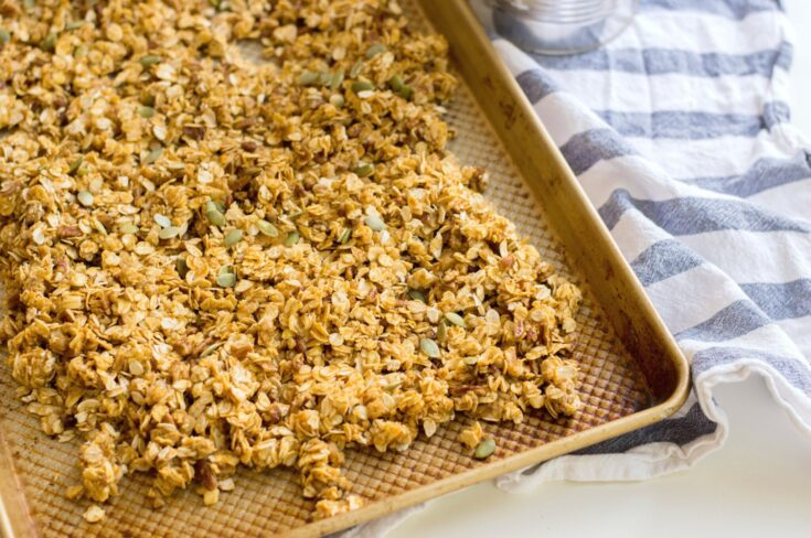 Pumpkin Maple Pecan Granola in a nonstick baking sheet.