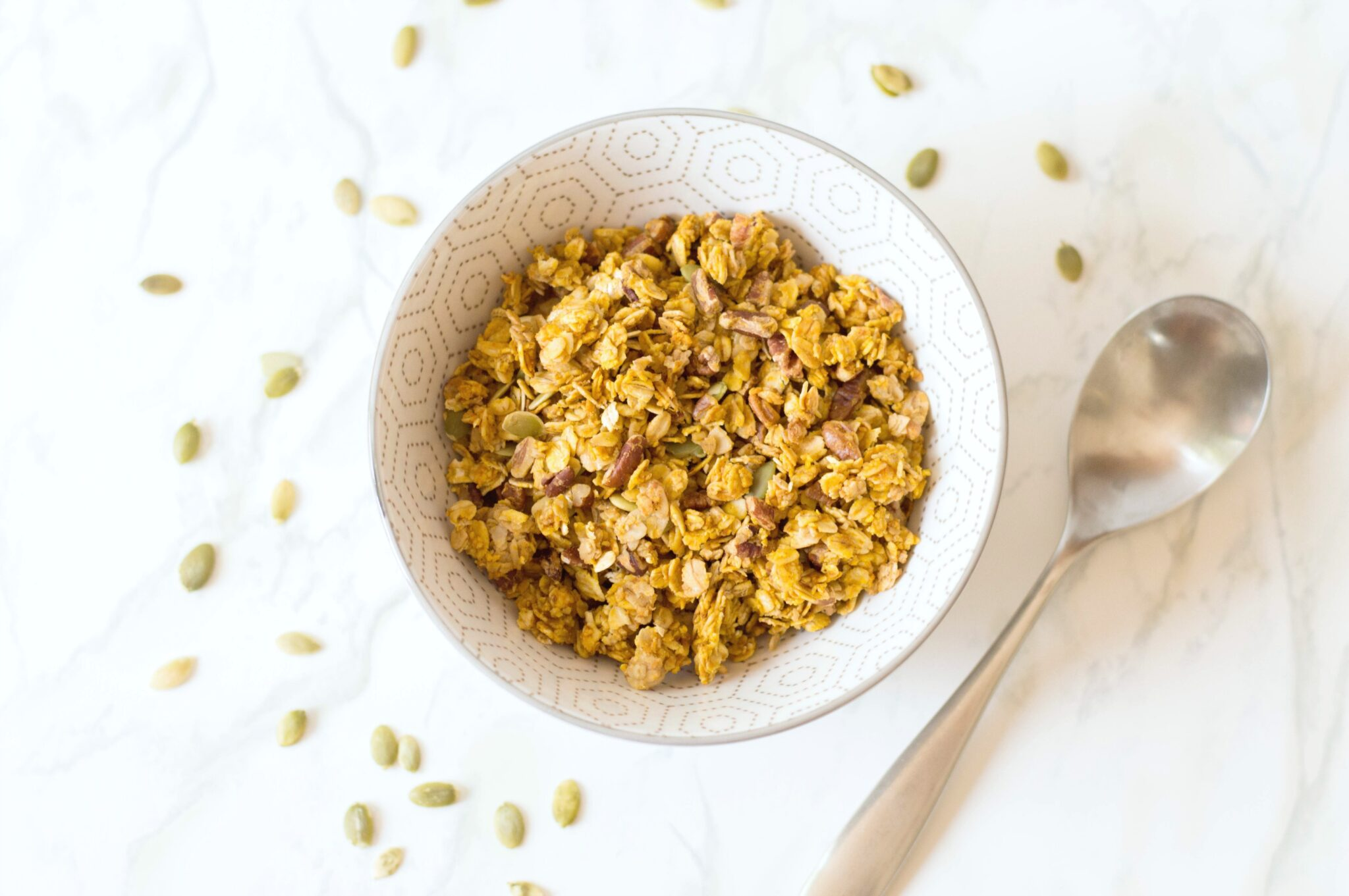 A bowl full of Pumpkin Maple Pecan granola, with a spoon.