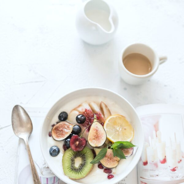 A healthy breakfast of a bowl with fruit and milk. There's a cup of coffee and a good book.