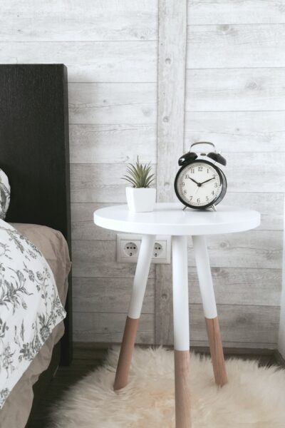 A side table with a clock sit in a guest bedroom.