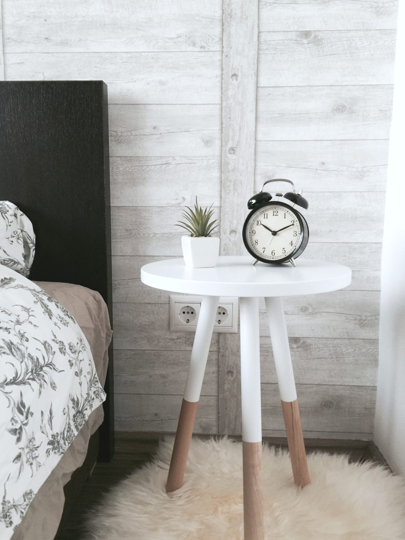 A bedroom with a nightstand and clock sit in a guest room. Find out how to create the perfect guest bedroom.