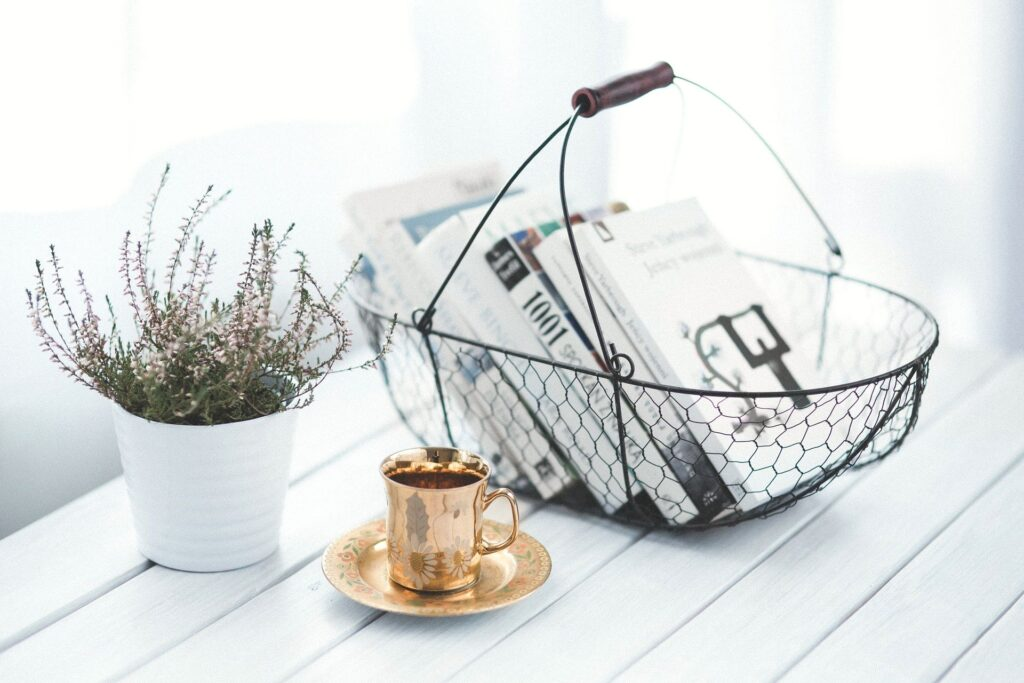 A basket filled with books on a white table. A gold mug and dish and flowers also sit on the table. Just an example of the ABCs of maintaining a happy home.