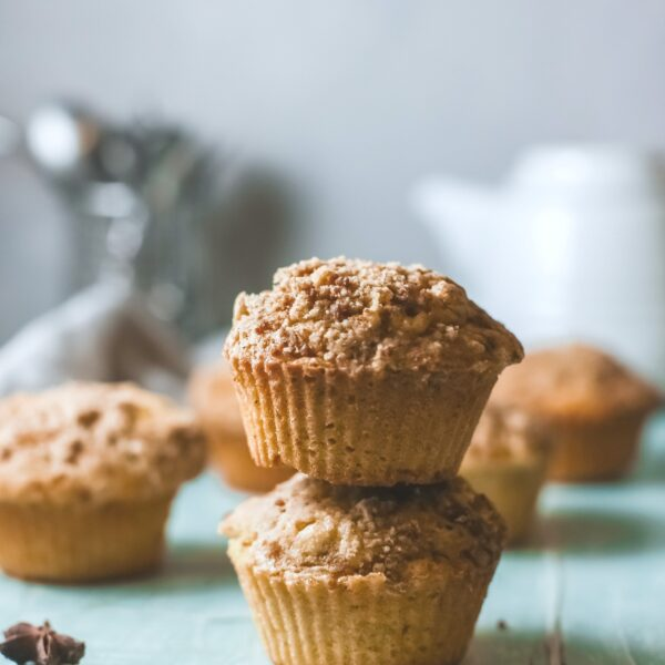 A stack of two pumpkin streusel muffins with more behind it. A tea pot and kitchen towel is seen.