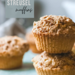A stack of two pumpkin streusel muffins with more behind it. A tea pot and kitchen towel is seen. A banner above it reads, 'Pumpkin Streusel Muffins.""