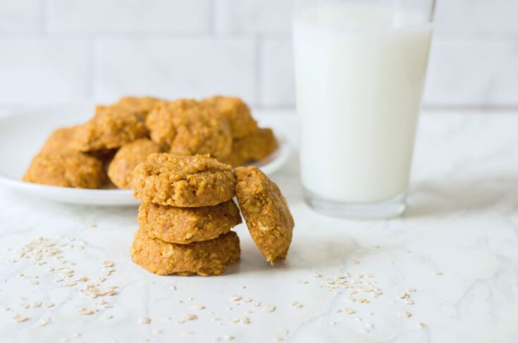 Cookies and milk with oats scattered on table top.