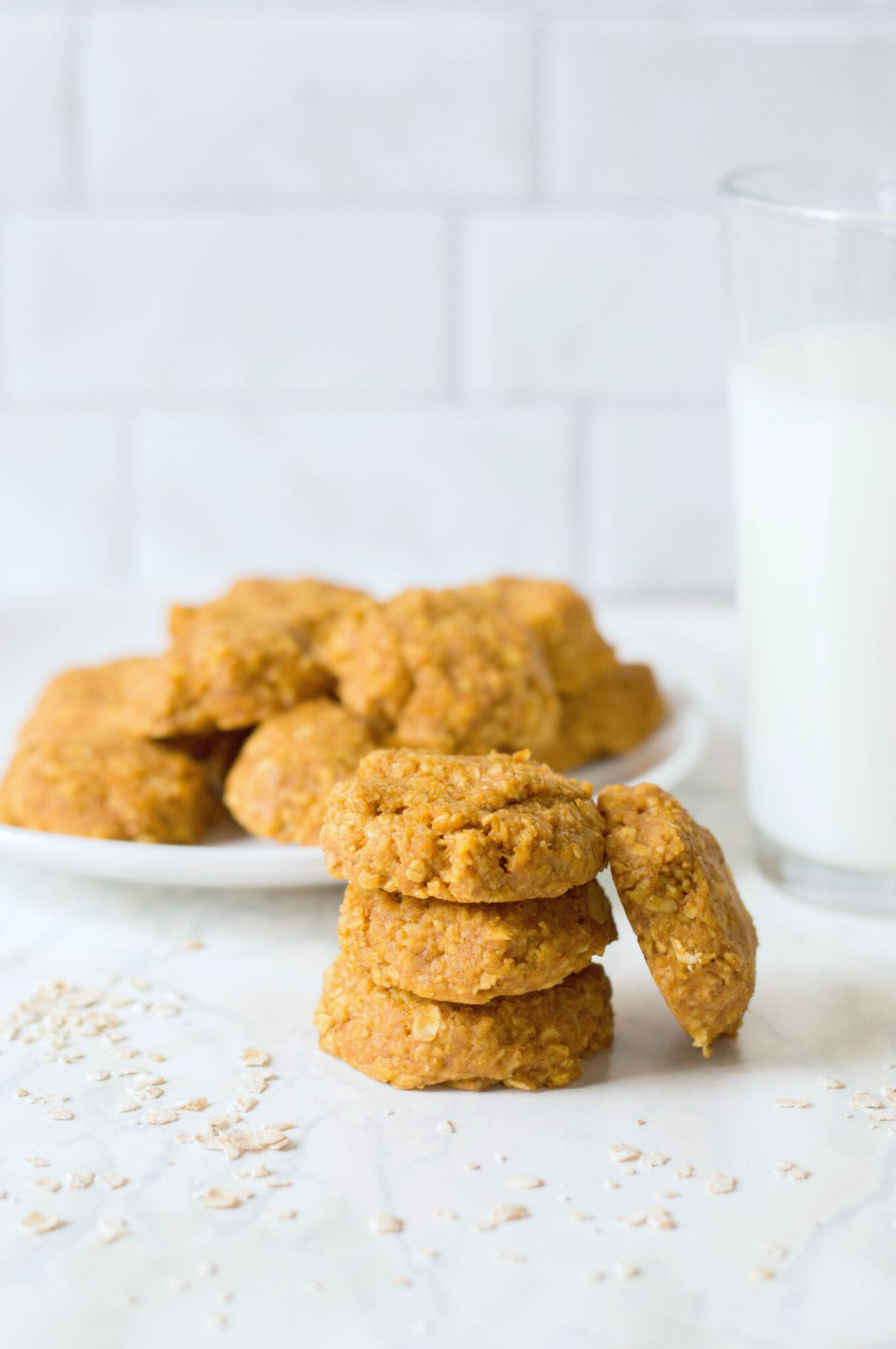 A plate of no-bake pumpkin oatmeal cookies and a stack of cookies on the side. There is a glass of milk against a white background.