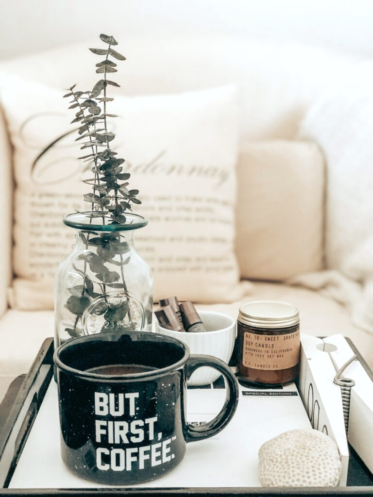 "A beautiful and cozy home, a tray with a coffee mug and other creature comforts sits on the coffee table. The mug reads, ""but, coffee first."""