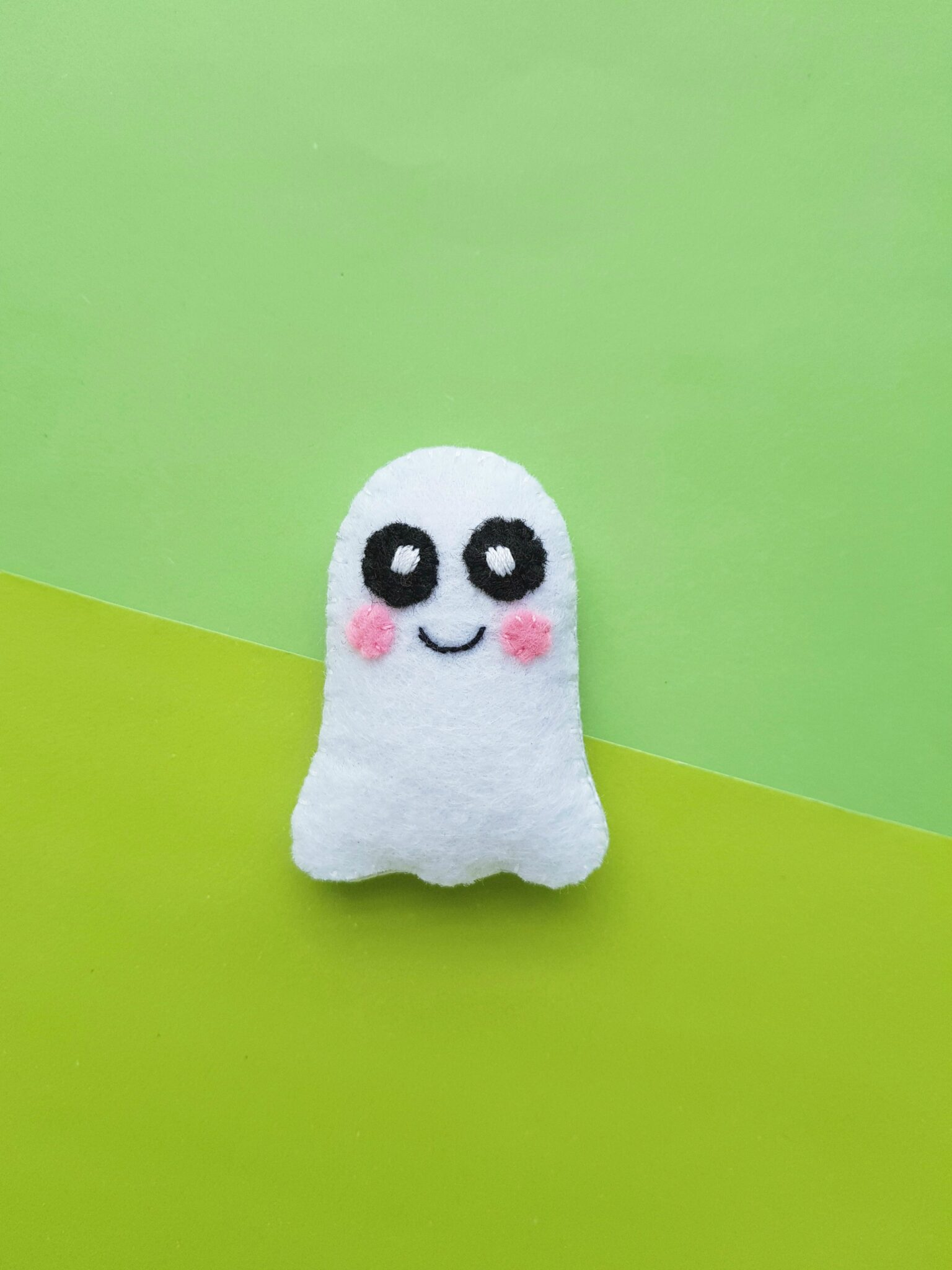 A cute little felt ghost plush sits on a light and dark green background. It has rosy cheeks and cute bright eyes.