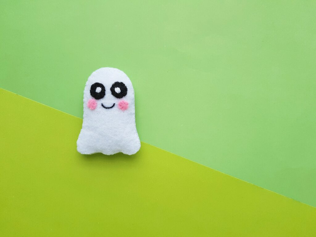 A cute felt ghost plushie is on a light and dark green background.