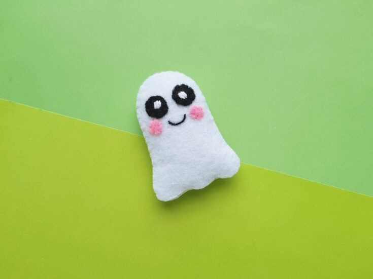 Finished felt ghost plush on a light and dark green background, it's tilted to the left.