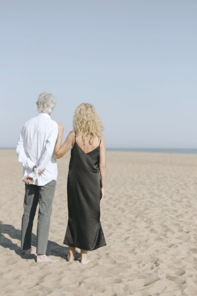 An older couple stand on a beach and look beyond the horizon. The woman has an arm on his shoulder.
