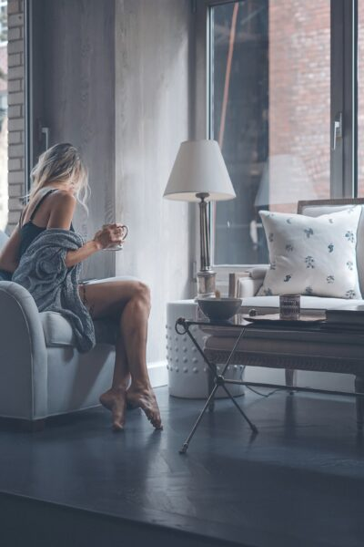 A blonde woman sits on a couch in her New York apartment while holding a mug.