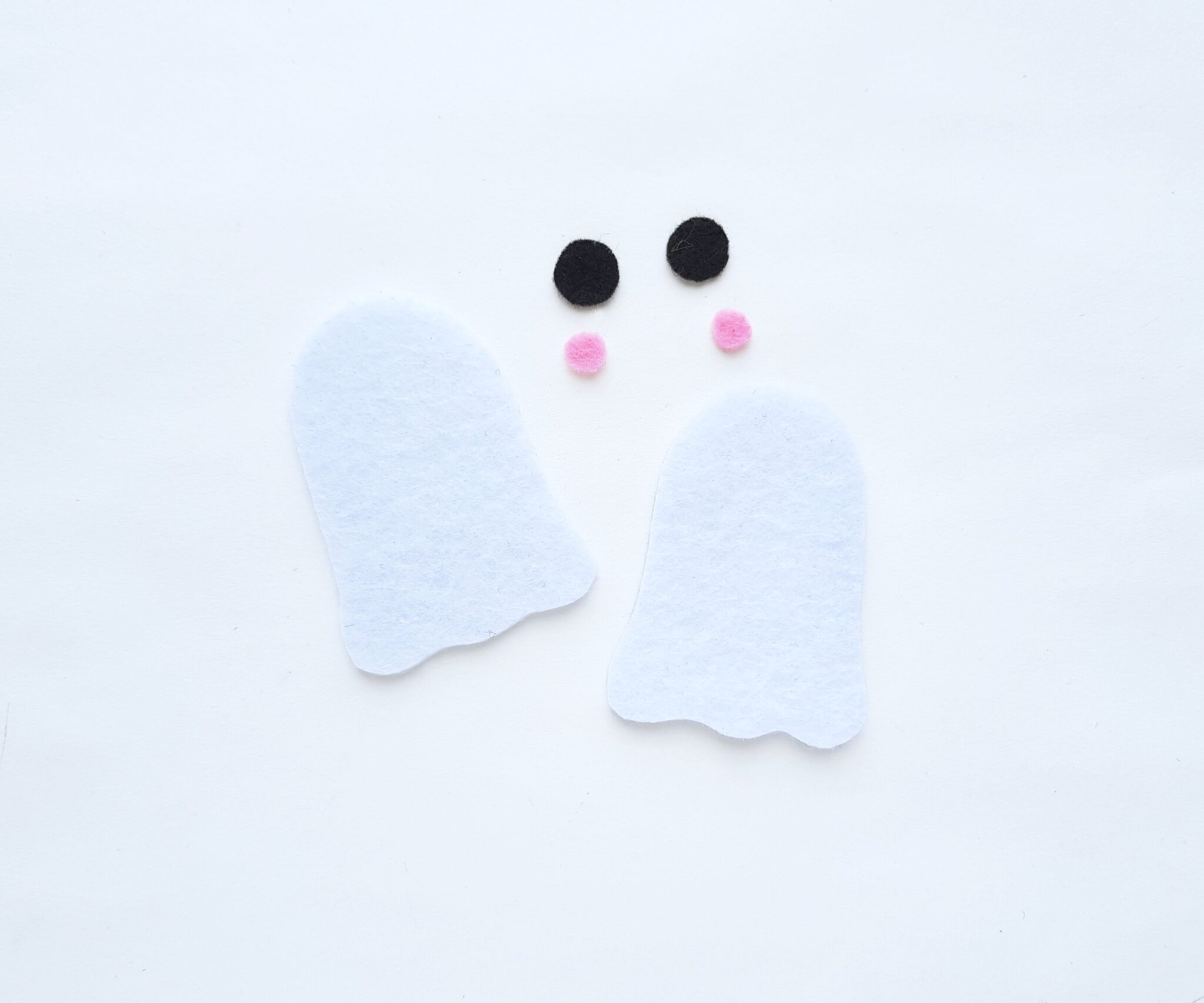 Two felt  pieces of white felt cut out in a ghost pattern, black eyes, and pink cheeks are cut out as well.