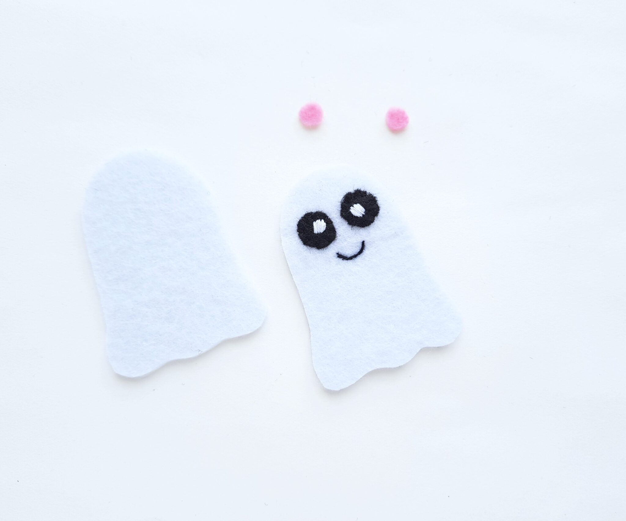 The eyes and smile are sewn onto the felt ghost plushie.