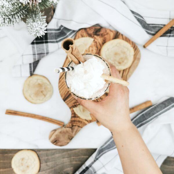 Flat lay of hand reaching in to pick up a Caramel Snickerdoodle Mocktail on an olive board. It's surrounded by snickerdoodle cookies and cinnamon sticks.