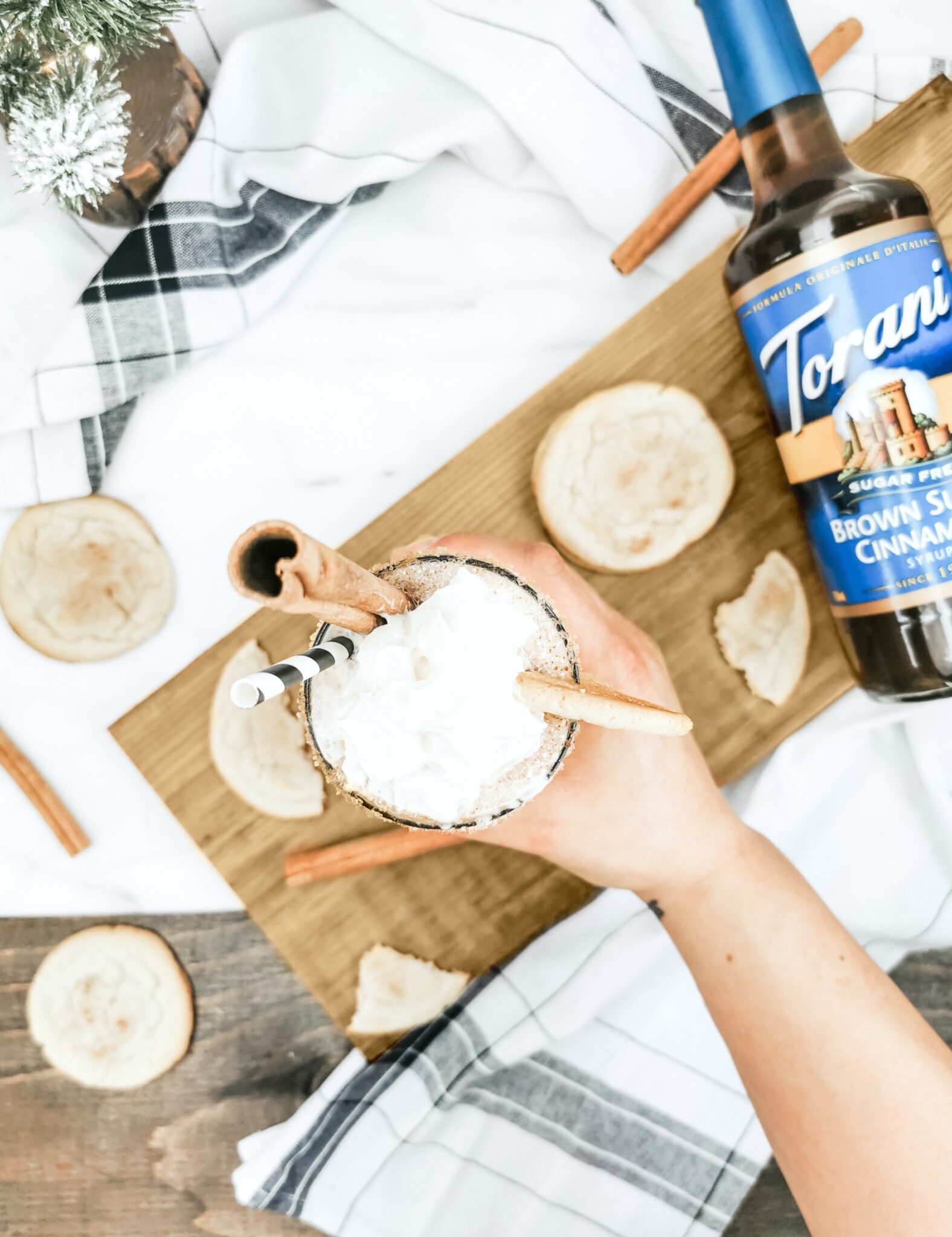 Flat lay of hand reaching for finished Caramel Snickerdoodle Mocktail. It' sits on a board and cookies, and a bottle of Torani syrup surrounds it.