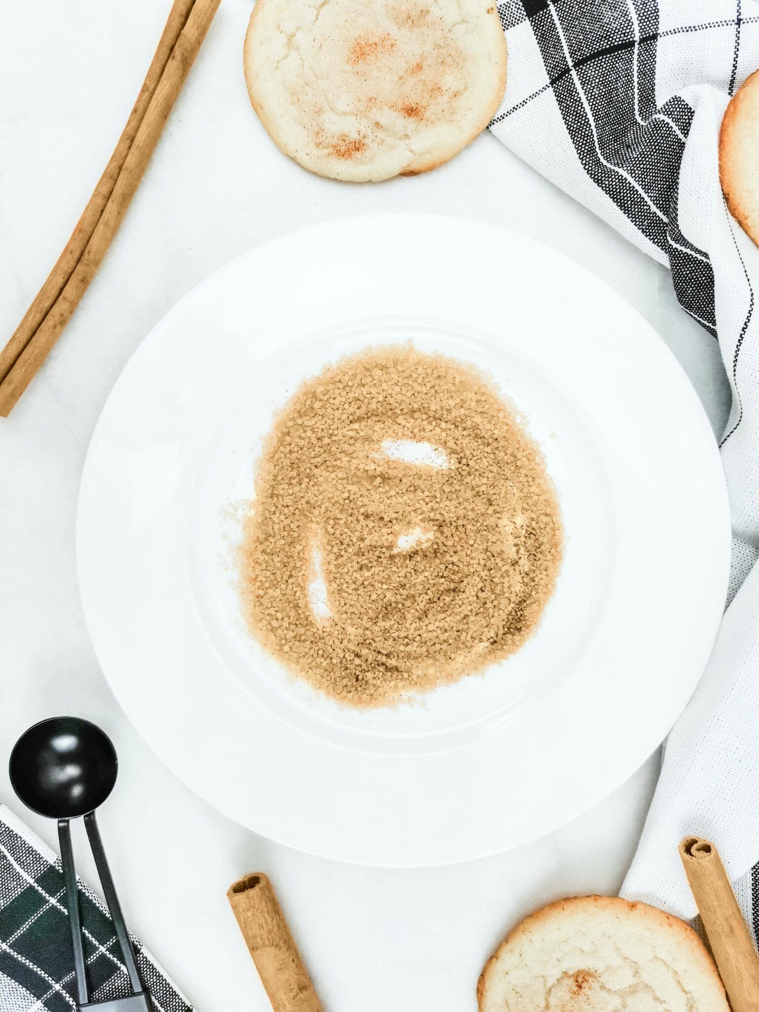 A flatlay picture with a plate with a stevia and turbinado raw sugar blend. This will be used for the rimming the glass for a Caramel Snickerdoodle Mocktail. Surrounding it are snickerdoodle cookies and cinnamon sticks.