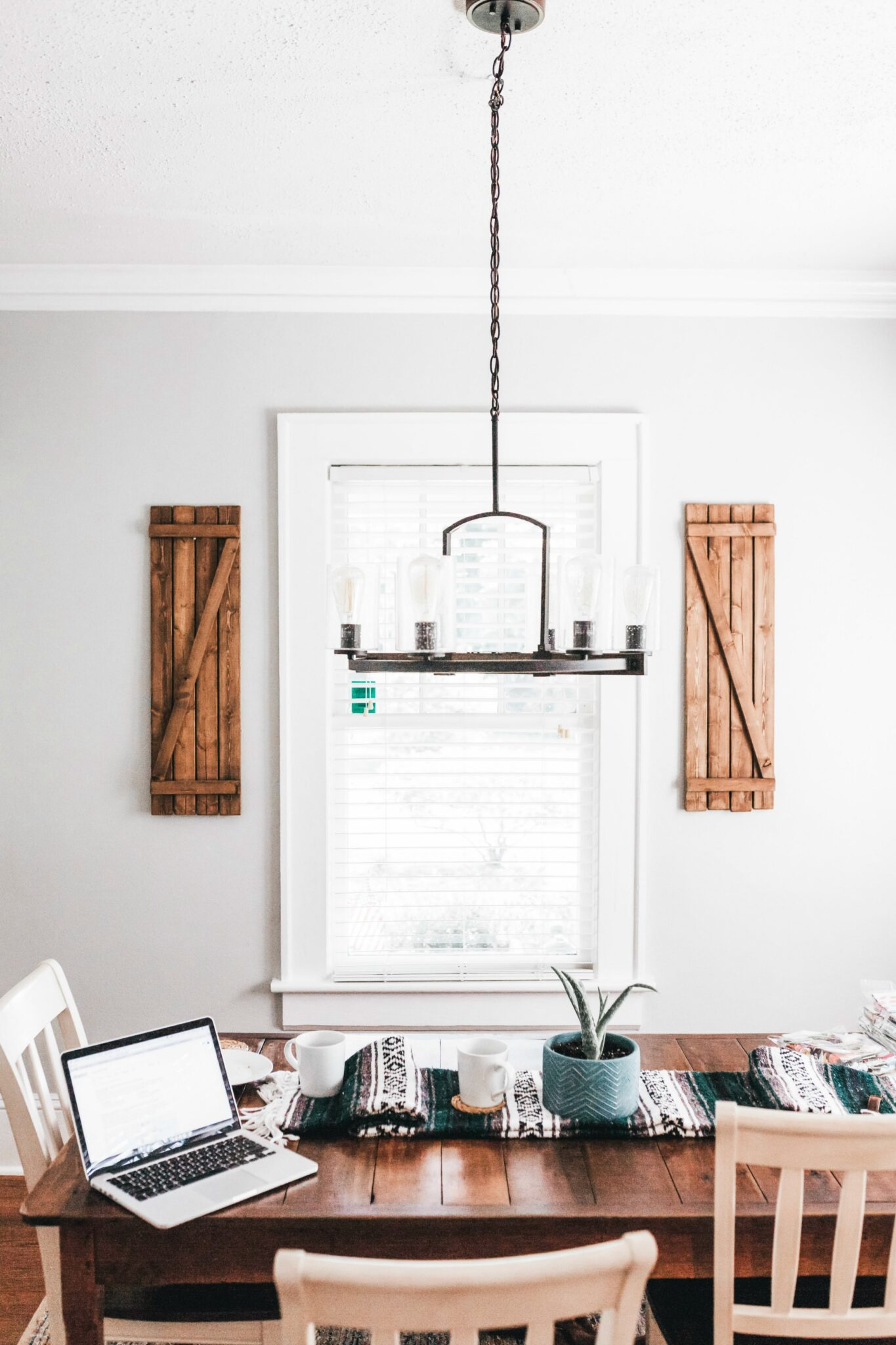 A beautiful farmhouse kitchen showing a bright window with blinds. A chandelier hangs and below is a makeshift office.