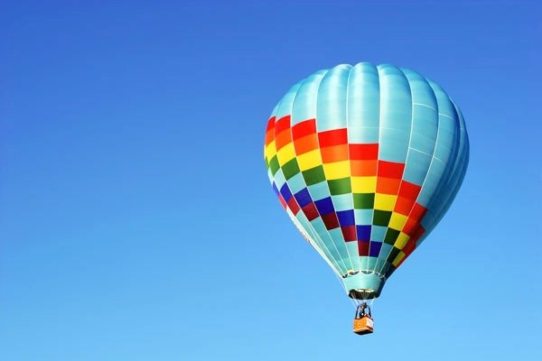 A hot air balloon ride against a blue sky. One of many socially-distanced experiences to enjoy.