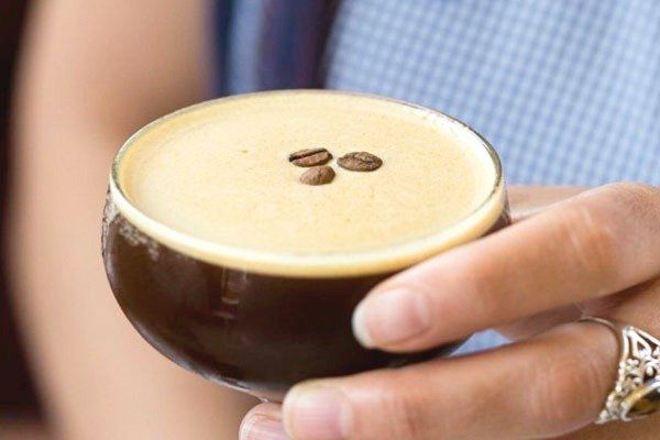 A cup of coffee topped with three coffee beans.